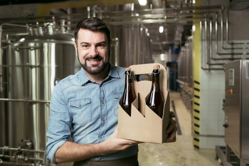 Zadowolone mężczyzna mienia butelki alkohol w browarze obrazy stock