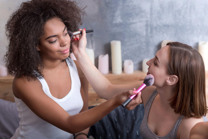 Zadowolone młode dziewczyny stawia makeup na each inny zdjęcie royalty free