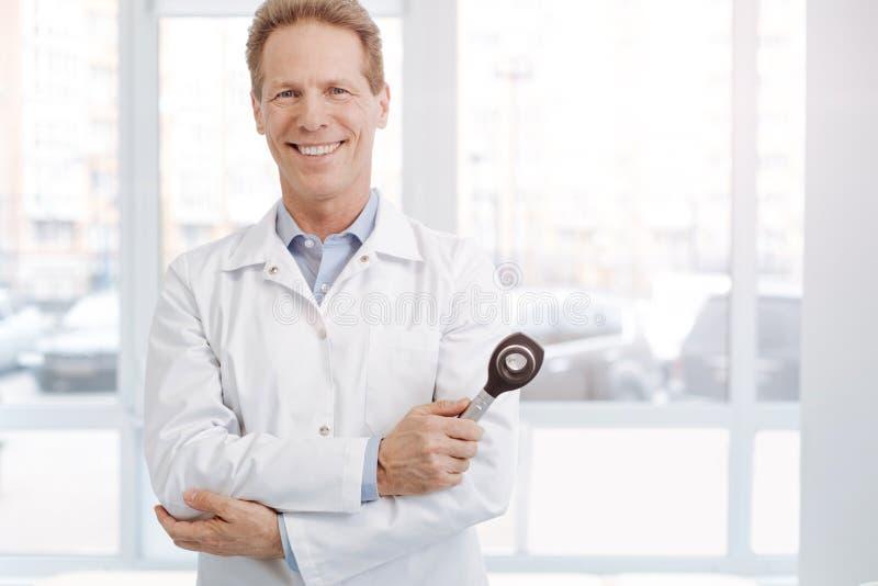 Zadowolonego starszego lekarza praktykującego mienia fachowy instrument przy pracą fotografia royalty free