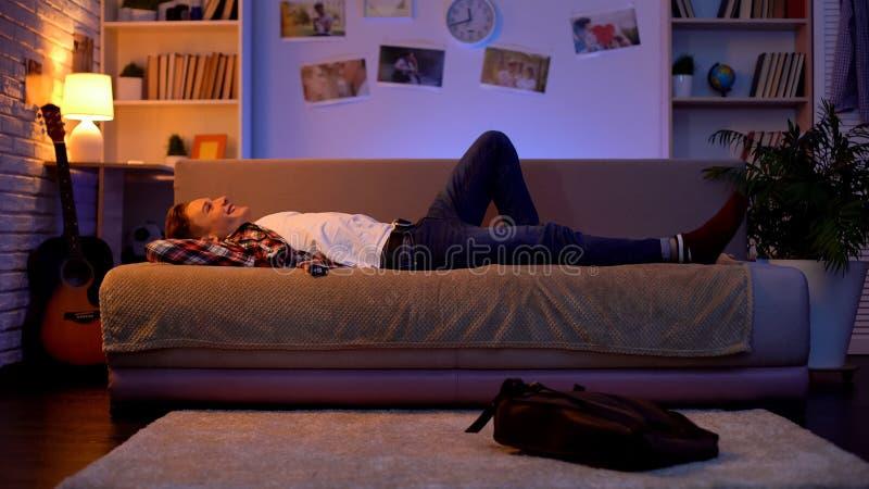Zadowolonego u?miechni?tego nastolatka przybycia studencki dom, ?garski puszek na kanapie, pierwszy praca fotografia royalty free