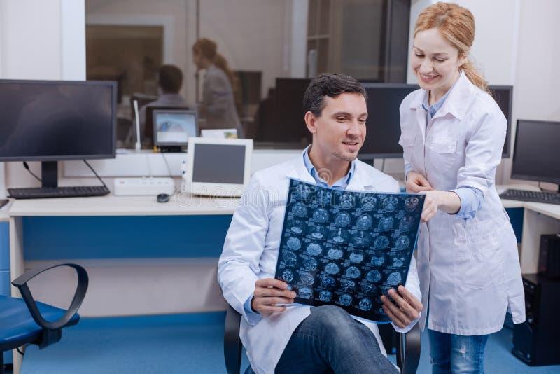 Zadowolonej kobiety doktorski wskazywać przy X promienia fotografią obraz stock