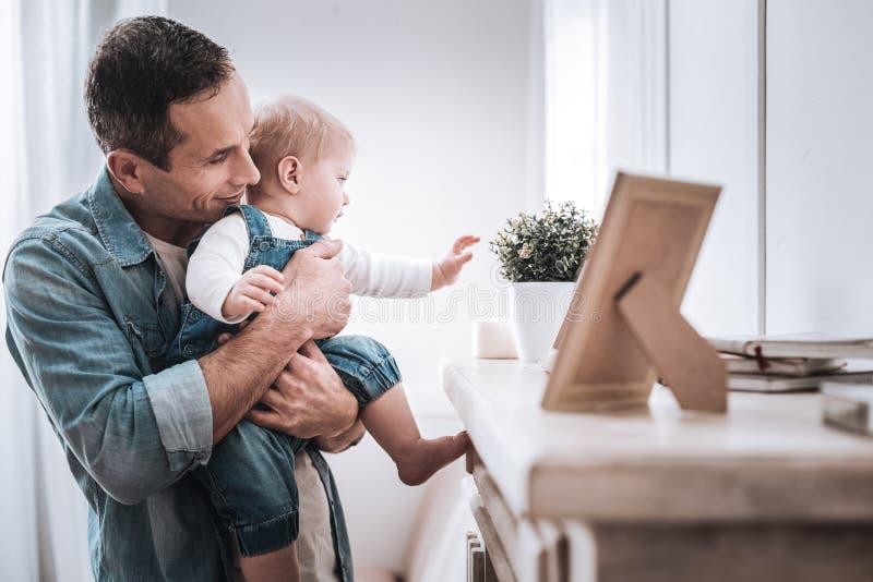 Zadowolony ładny mężczyzna trzyma jego dziecka obrazy royalty free