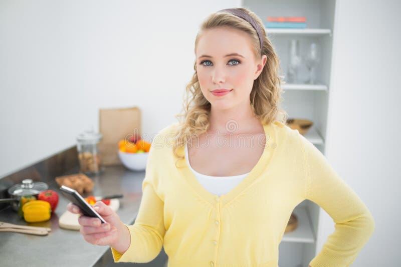 Zadowolony śliczny blondynki mienia smartphone zdjęcia royalty free