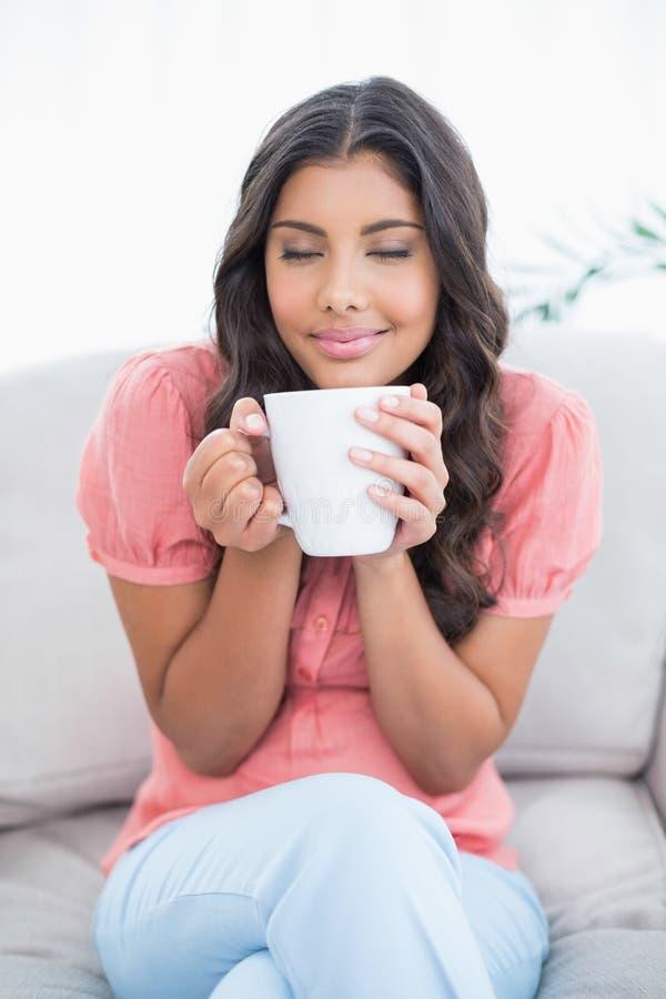 Zadowolony śliczny brunetki obsiadanie na leżanki mienia kubku zdjęcie royalty free