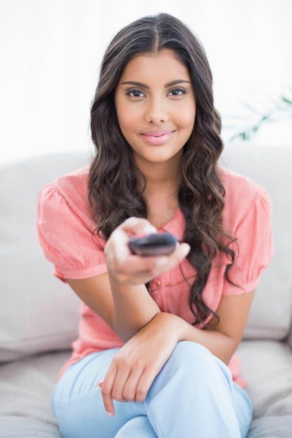 Zadowolony śliczny brunetki obsiadanie na leżanki mienia pilocie zdjęcia royalty free