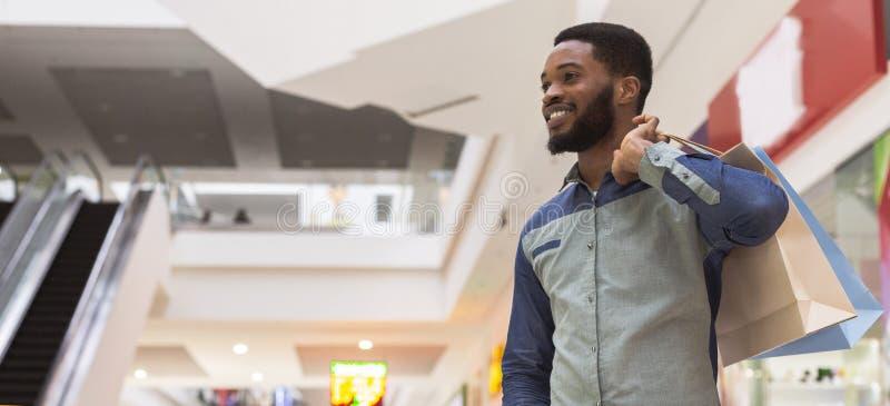 Zadowolony afrykański facet patrzeje kopii przestrzeń z papierowymi torbami obraz royalty free