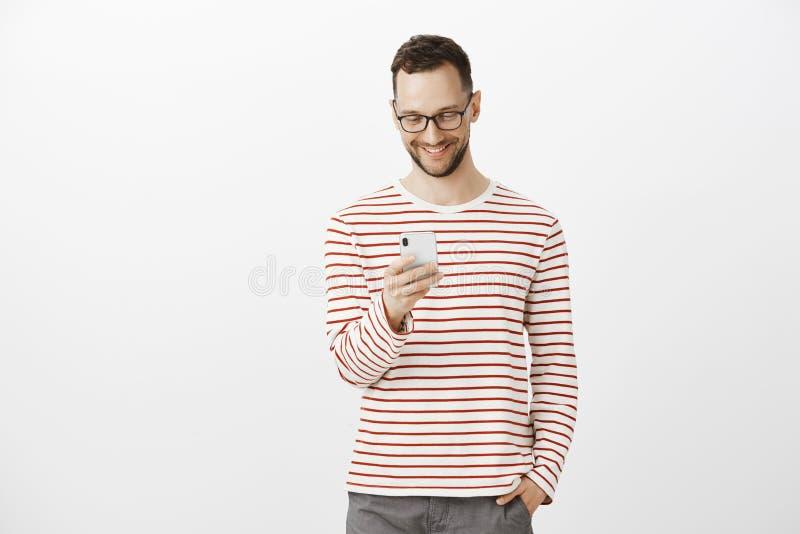 Zadowolony beztroski przystojny mężczyzna z szczecina w szkłach, trzyma rękę w kieszeni podczas gdy brosing w sieci przez smartph obrazy stock