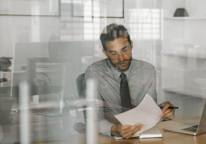 Zadowolony biznesmena obsiadanie przy pracą przegląda pisać pomysły fotografia royalty free