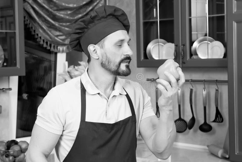 Zadowolony brodaty kucharz wącha świeżego pieprzu w Burgundy kapeluszu fotografia stock