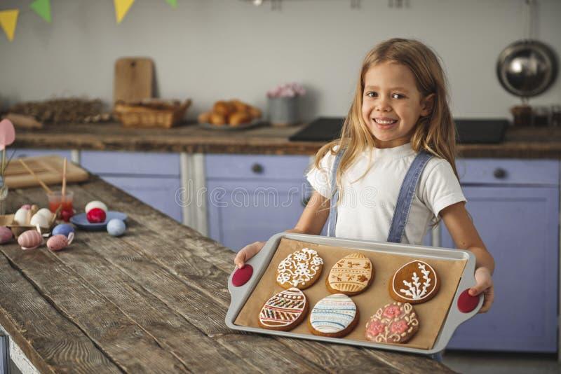 Zadowolony dzieciak pokazuje tacę ciastka pełno obraz royalty free