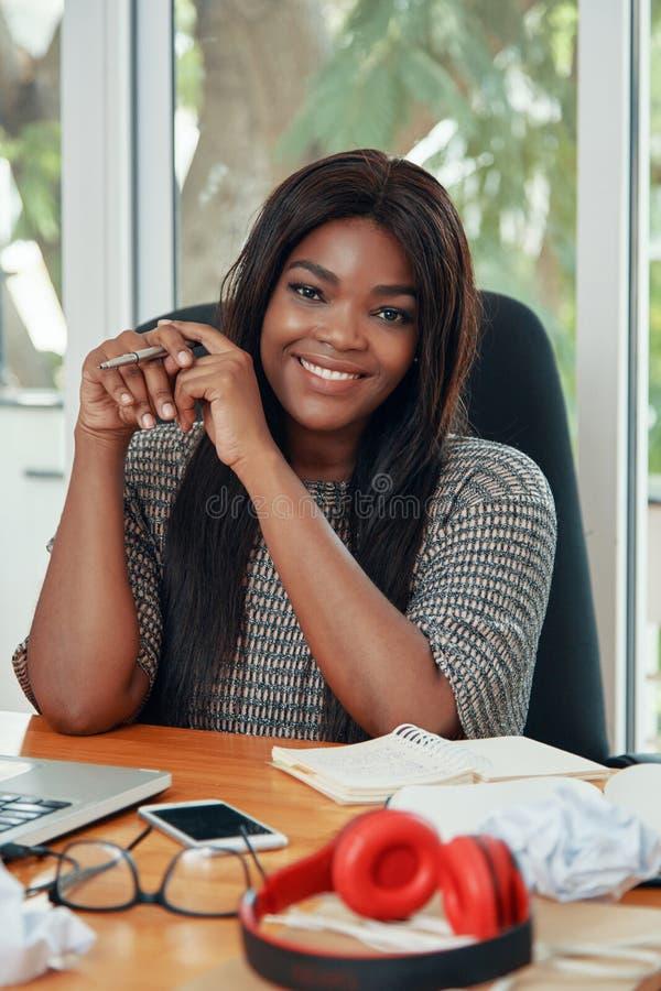 Zadowolony etniczny bizneswoman przy pracującym biurkiem zdjęcia royalty free