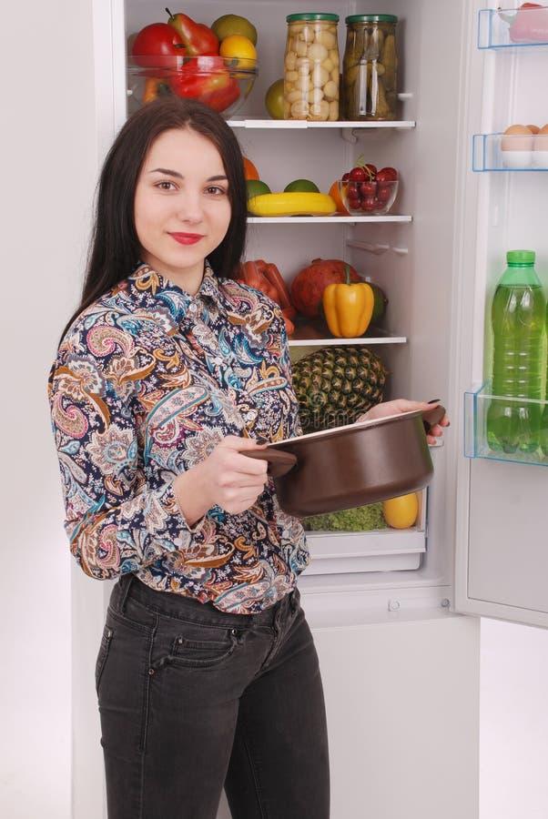 Zadowolony gospodyni domowej blisko wypełniający fridge zdjęcie stock