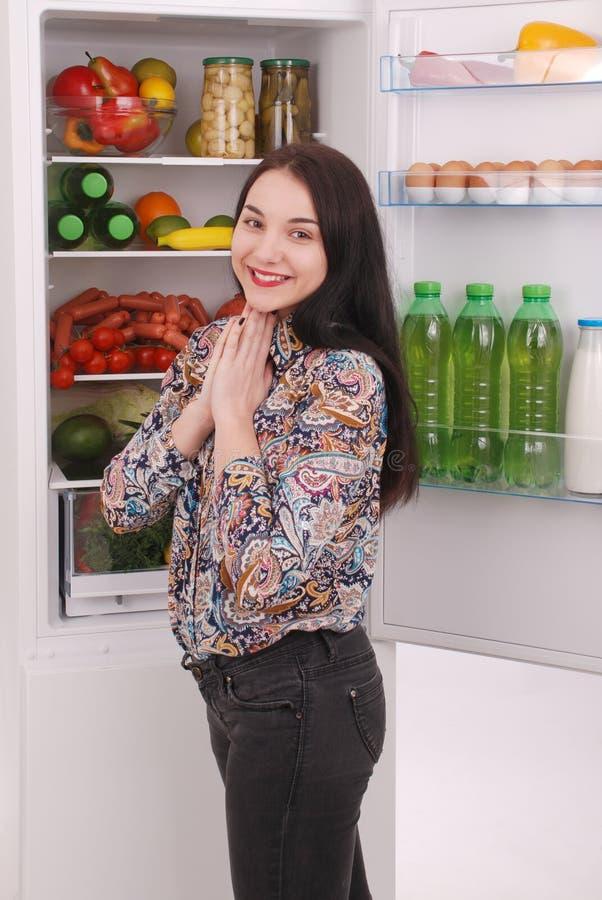 Zadowolony gospodyni domowej blisko wypełniający fridge obrazy royalty free