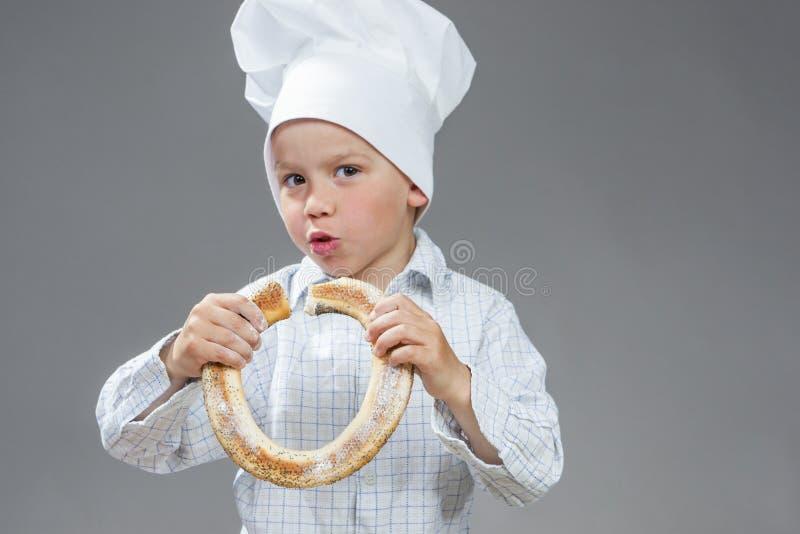 Zadowolony Kaukaski Little Boy Je Świeżego pączka Chlebową rolkę Pozować W Kulinarnym kapeluszu obraz stock