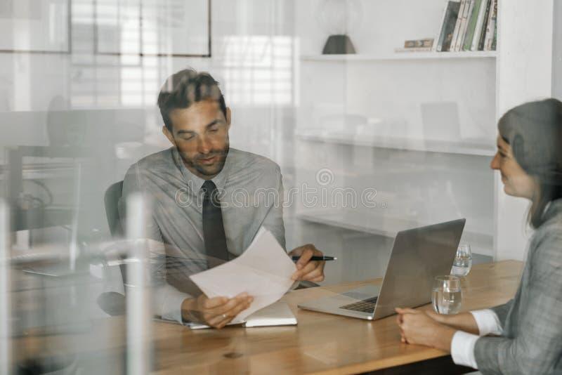 Zadowolony kierownik czyta wnioskodawcy życiorys podczas wywiadu zdjęcia royalty free