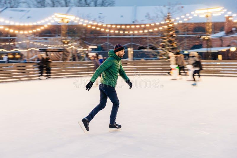 Zadowolony mężczyzna w zielonej kurtce, jest ubranym łyżwy, iść jeździć na łyżwach na lodzie, fotografia stock