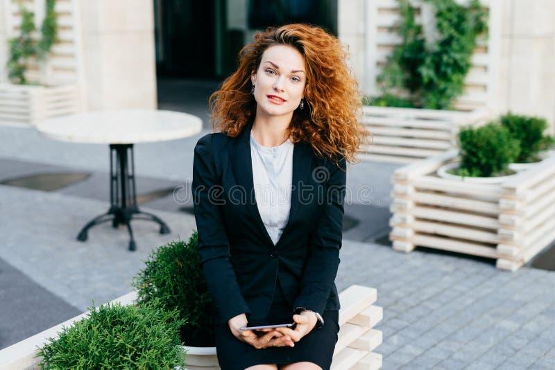 Zadowolony młody bizneswoman z kędzierzawym włosy, będący ubranym białą bluzkę i czarnego kostium siedzi przy plenerową restaurac fotografia stock