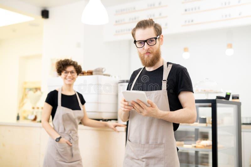 Zadowolony młody kelner w sklepie z kawą zdjęcia royalty free