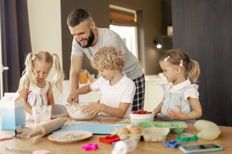 Zadowolony pozytywny mężczyzny kucharstwo z jego dziećmi fotografia royalty free