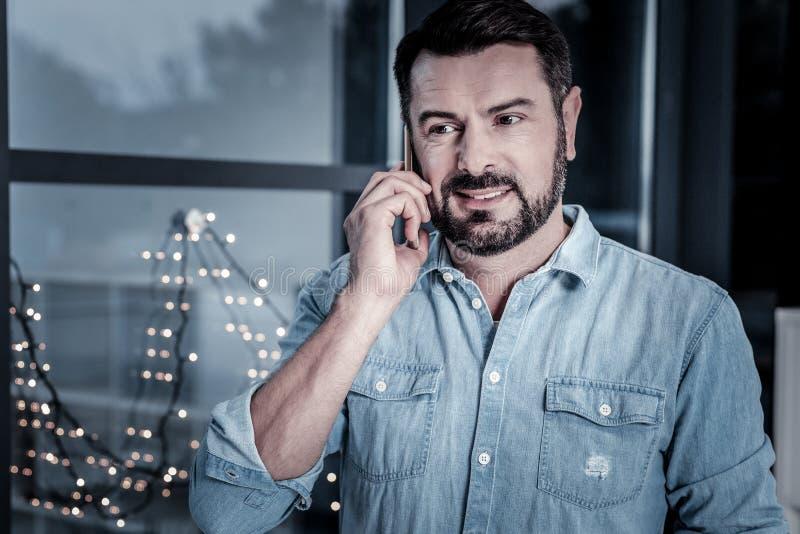 Zadowolony przyjemny mężczyzna używa telefon komórkowego i komunikować fotografia stock