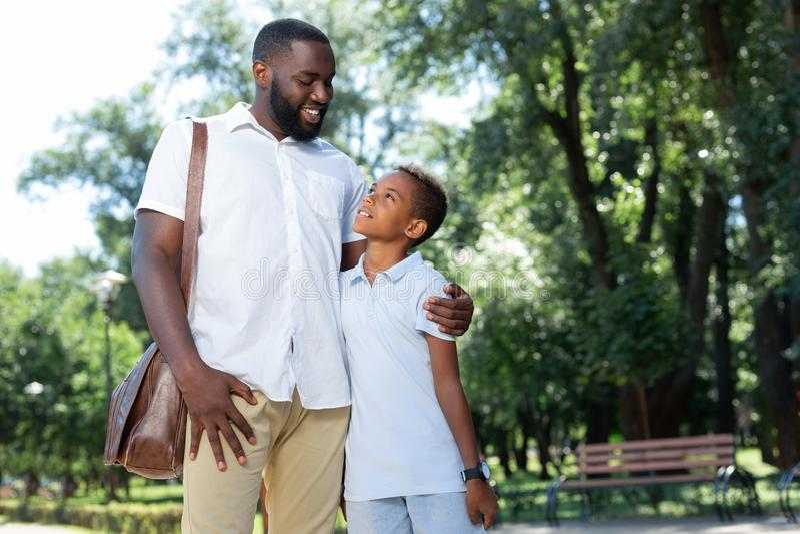 Zadowolony radosny mężczyzna ściska jego ukochanego syna fotografia royalty free
