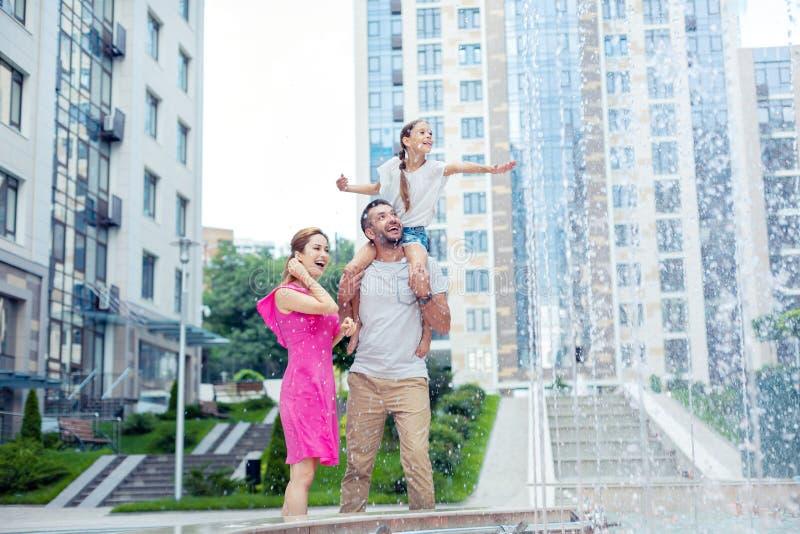 Zadowolony szczęśliwy rodzinny patrzejący fontannę fotografia royalty free