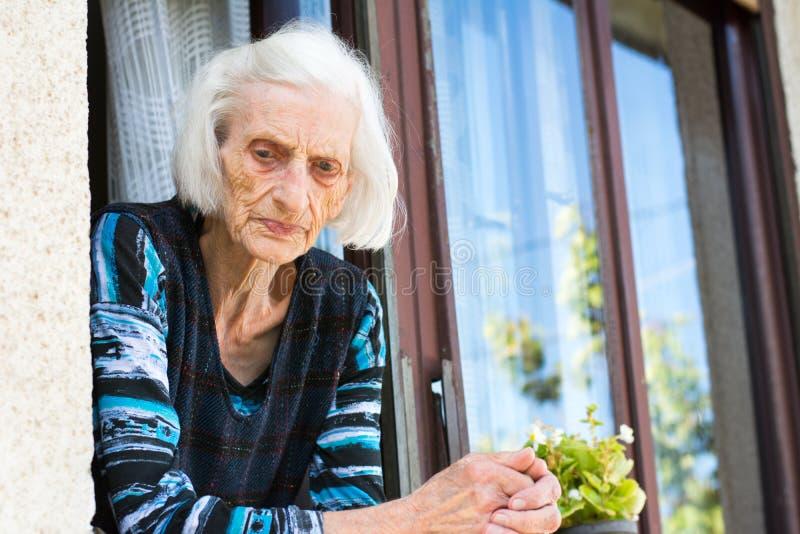 Zadumana babcia przy domowym okno obraz royalty free