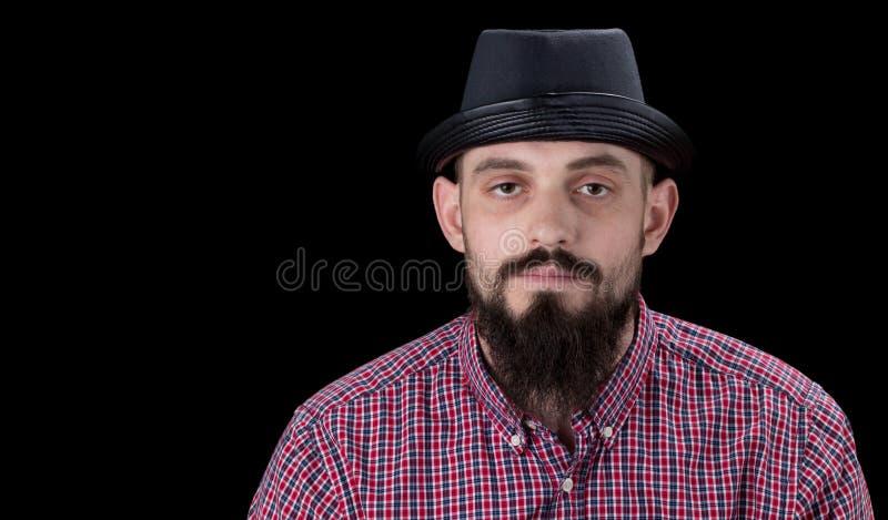 Zadumana brodata samiec ubierał w runo koszula kapeluszowym pozować i obraz stock