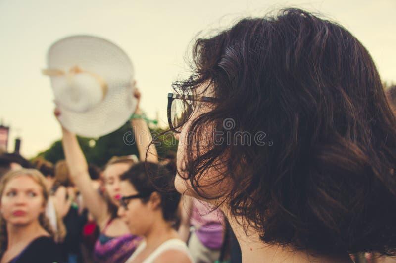 Zadumana brown kędzierzawego włosy młoda dziewczyna przy fest outdoors fotografia stock