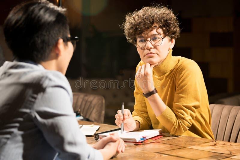 Zadumana dama słucha kolega skupiał się na myślach zdjęcie stock