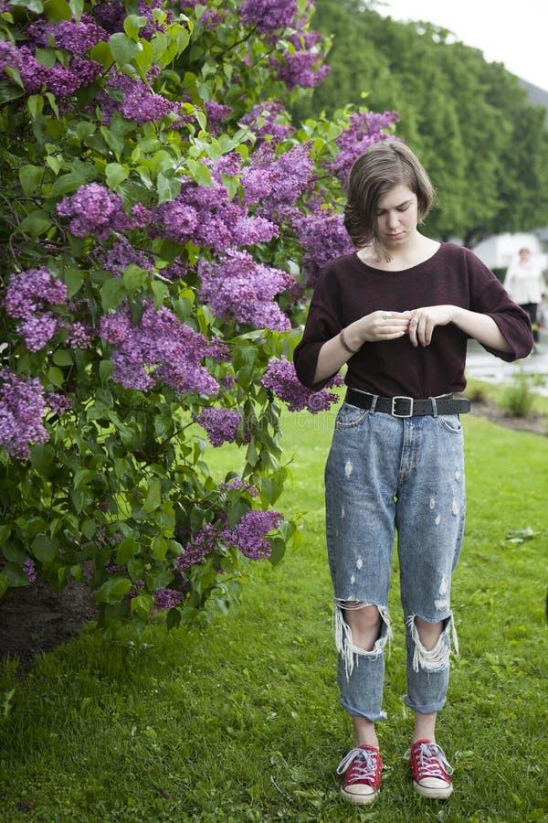 Zadumana dziewczyna pozuje w lilych krzakach w parku zdjęcie stock