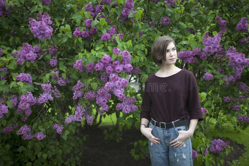 Zadumana dziewczyna pozuje w lilych krzakach w parku zdjęcia royalty free