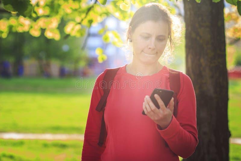 Zadumana dziewczyna z smartphone w rękach w miasto parku kobieta jest przyglądająca ekran telefon komórkowy obrazy royalty free