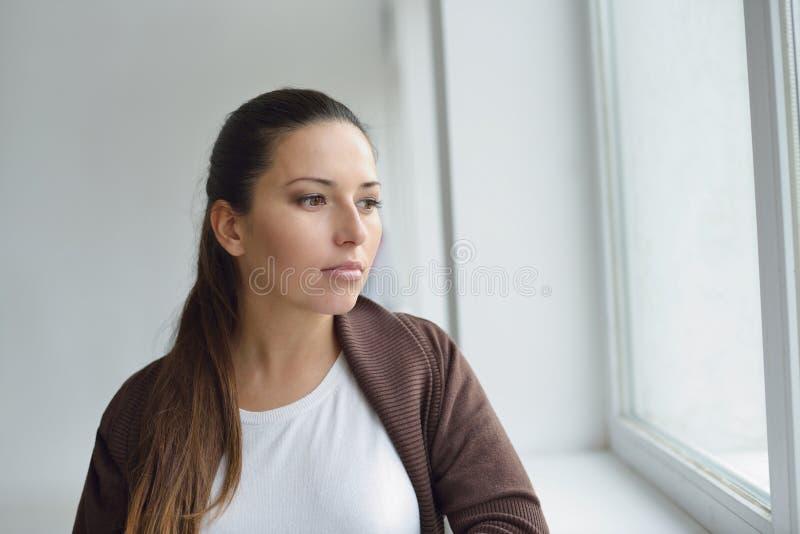 Zadumana kobieta blisko okno zdjęcia royalty free