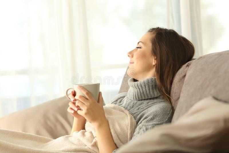 Zadumana kobieta relaksuje w domu w zimie fotografia royalty free