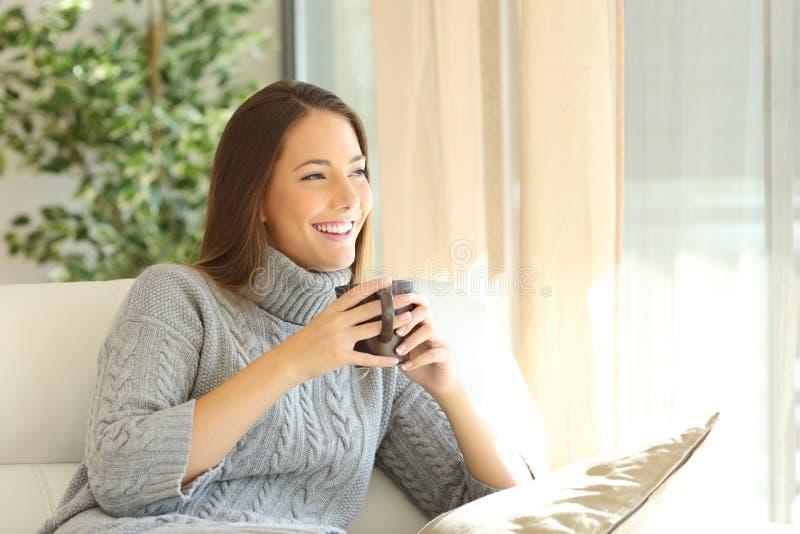 Zadumana kobieta w zimie w domu fotografia royalty free