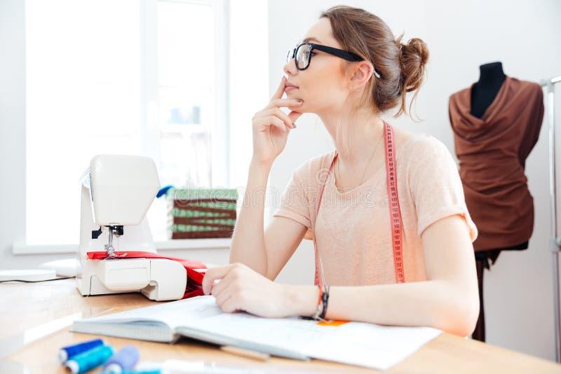Zadumana kobiety szwaczka pracuje przy główkowaniem i stołem zdjęcia royalty free