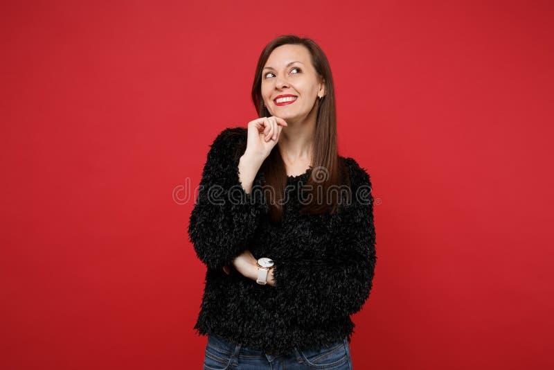 Zadumana młoda kobieta w czarnym futerkowym pulowerze przyglądającym w górę, stawiająca ręka podpiera w górę podbródka odizolowyw obrazy royalty free