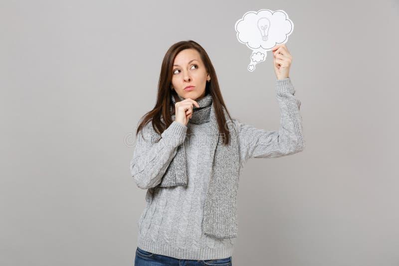 Zadumana młoda kobieta w szarym pulowerze, szalik stawiająca ręka podpiera w górę podbródka na, chwyt mówi chmurę z lightbulb odi fotografia stock