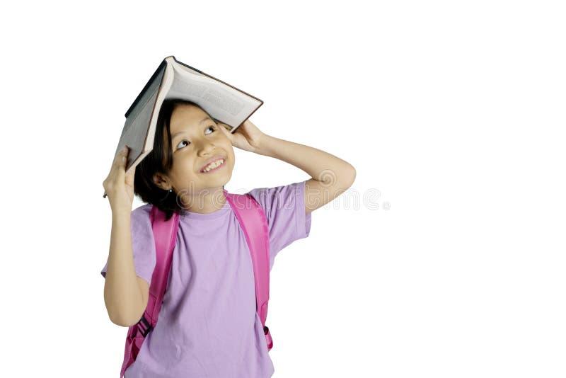 Zadumana mała dziewczynka stawia książkę na jej głowie obraz stock