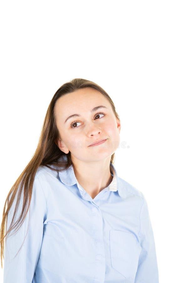 Zadumana marzycielska młoda kobieta przyglądająca w górę odosobnionego na biel ściany tła studia portrecie zdjęcie royalty free