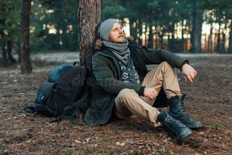 Zadumana modnisia faceta podróżomania z turystycznym plecakiem cieszy się spokój podczas rekonesansowego natury środowiska, zdjęcia royalty free