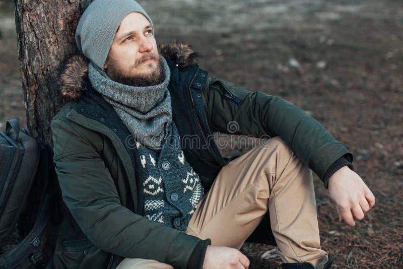 Zadumana modnisia faceta podróżomania z turystycznym plecakiem cieszy się spokój podczas rekonesansowego natury środowiska, obrazy stock