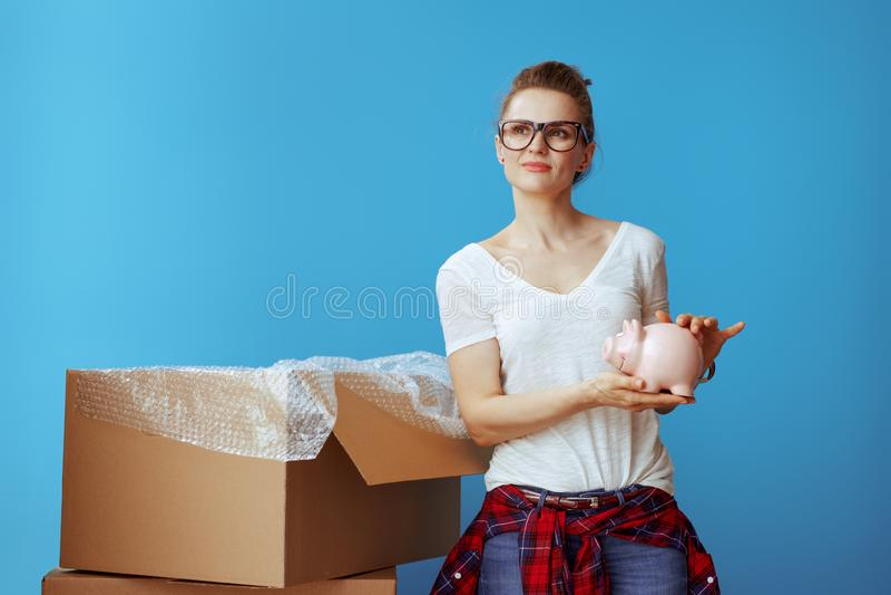 Zadumana nowożytna kobieta w białej koszulce na błękicie z piggybank zdjęcia stock