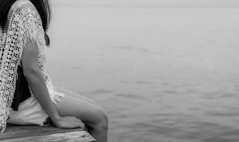 Zadumana osamotniona dorosła Azjatycka kobieta Tylny widok kobieta z smutnym uczuciem w czarny i biały scenie przy morzem Przygnę zdjęcie stock