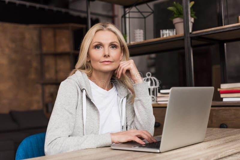 zadumana w średnim wieku kobieta używa laptop fotografia royalty free