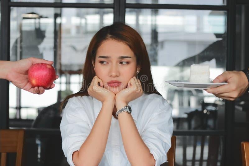 Zadumana zaakcentowana Azjatycka kobieta wybiera między jabłczanym lub niezdrowym tortem na biurku Zdrowy styl życia i dieting po zdjęcie stock
