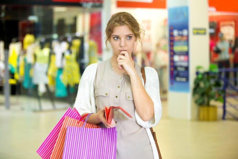 Zadumanego młodej kobiety mienia pusty portfel po robić zakupy obrazy royalty free