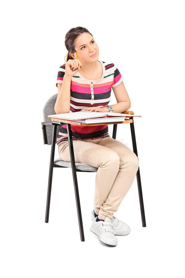 Zadumany żeńskiego ucznia obsiadanie na szkolnym biurku zdjęcie stock