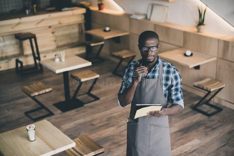 zadumany amerykanin afrykańskiego pochodzenia kelner pracuje rozkaz i bierze fotografia royalty free